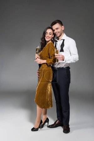 smiling couple hugging and holding champagne glasses on grey