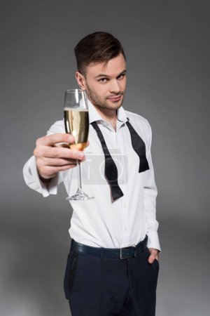 handsome man toasting with glass of champagne isolated on grey