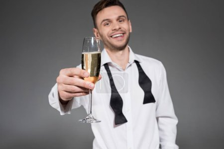 handsome cheerful man toasting with champagne glass isolated on grey