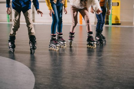 Photo for Cropped view of children preparing to start moving in roller skates - Royalty Free Image