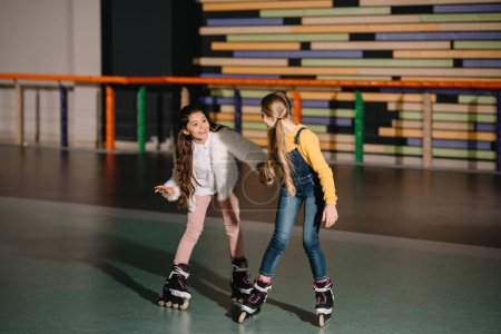 Photo for Two smiling long haired friends preparing to start moving on roller skates - Royalty Free Image