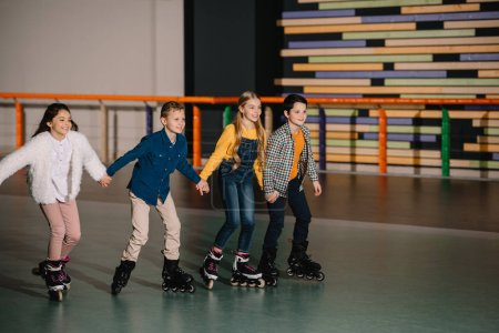 Photo for Group of smiling children skating in roller rink with holding hands - Royalty Free Image
