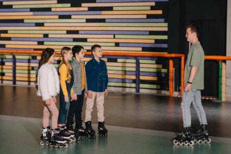 Foto de Niños sonrientes en patines escuchando las instrucciones de entrenadores - Imagen libre de derechos