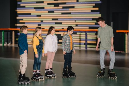 Foto de Joven instructor mostrando patinaje plantea a los niños atentos - Imagen libre de derechos