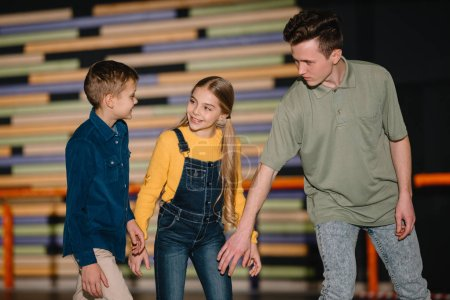Photo for Selective focus of handsome young trainer explaining skating technics to smiling children - Royalty Free Image