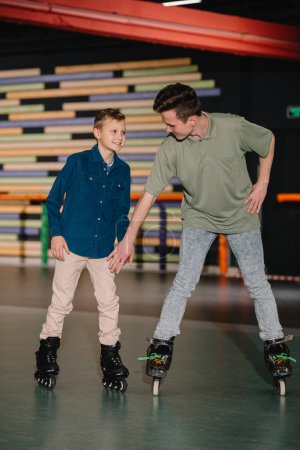 Photo for Handsome young trainer giving skating instructions to smiling boy - Royalty Free Image