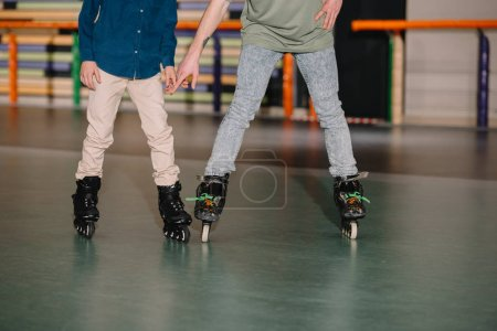 Photo for Cropped view of trainer and boy in roller skates - Royalty Free Image