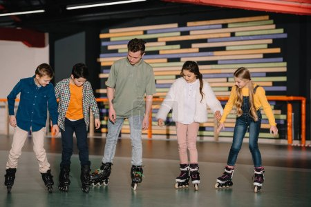 Photo for Young trainer showing skating basic technics to attentive children - Royalty Free Image
