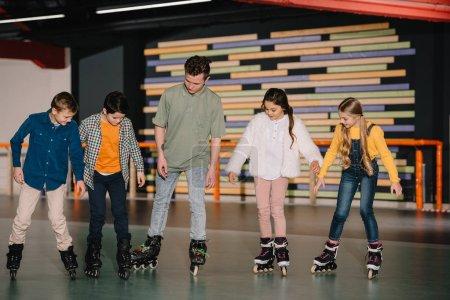 Foto de Técnicas básicas de la muestra joven entrenador patinaje para niños atentos - Imagen libre de derechos