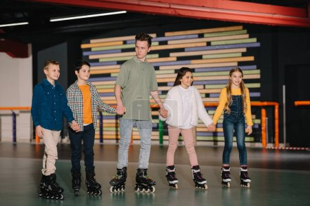 Photo for Pretty smiling children with handsome trainer standing in roller rink and holding hands - Royalty Free Image