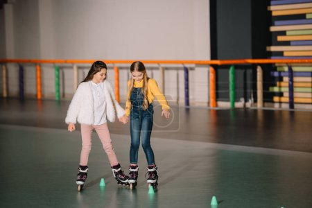 Photo for Beautiful kids practicing rolling skating while holding hands - Royalty Free Image