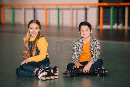 Photo for Indoor shot of smiling kids in roller skates having fun together - Royalty Free Image