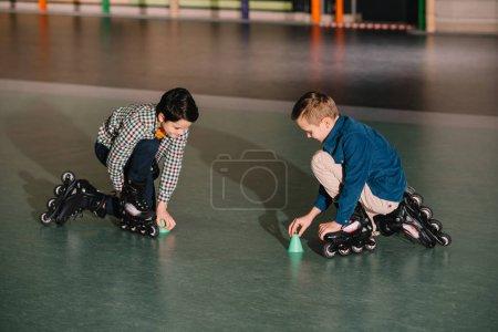 Foto de Niños de rodillo en patines negro entrenando juntos en el gimnasio - Imagen libre de derechos