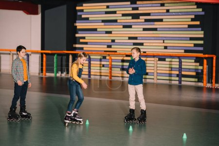 Photo for Preteen roller skaters practicing skating on rink together - Royalty Free Image