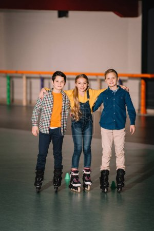 Photo for Full length shot of smiling kids hugs on skating rink - Royalty Free Image