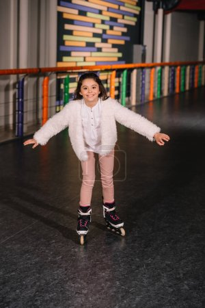 Photo for Little roller skater skating with sincere smile - Royalty Free Image