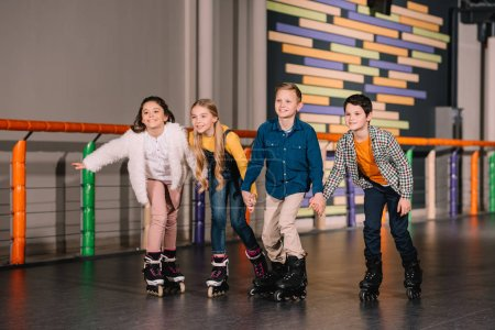 Photo for Four smiling kids holding hands while skating together - Royalty Free Image