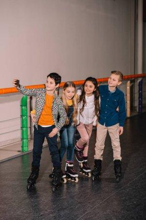 Foto de Niños en patines haciendo selfie después del entrenamiento en pista de patinaje - Imagen libre de derechos