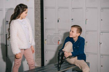 Photo pour Tir intérieur des enfants mettant en rollers au vestiaire - image libre de droit