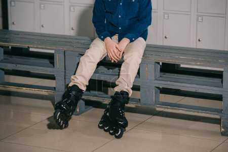 Photo for Partial shot of boy in black roller skates sitting on bench - Royalty Free Image