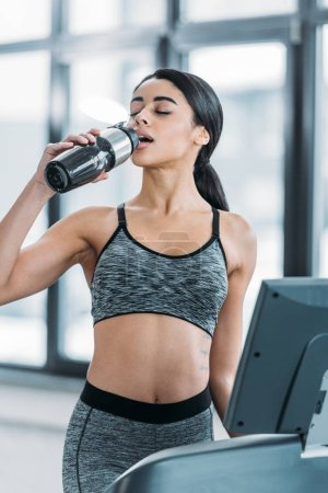 young sporty african american woman drinking water and exercising on treadmill in gym