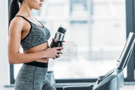 Photo for Cropped shot of sporty african american girl holding sports bottle and training on treadmill in gym - Royalty Free Image