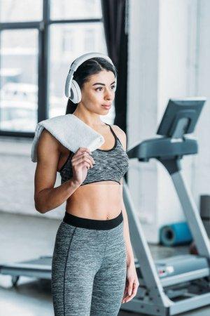 atractiva joven afroamericana deportista en auriculares sosteniendo la toalla y mirando hacia otro lado en el gimnasio