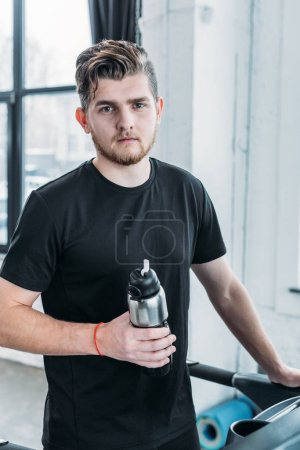 Photo for Handsome young man holding sports bottle and looking at camera in gym - Royalty Free Image