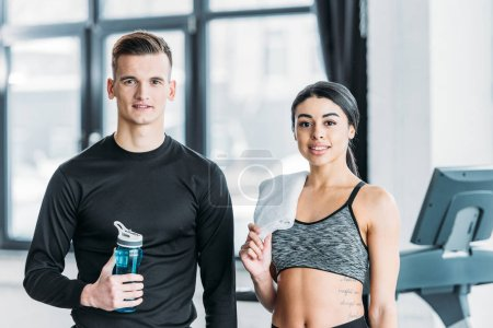 Photo for Handsome man with bottle of water and beautiful african american woman with towel standing together and smiling at camera in gym - Royalty Free Image