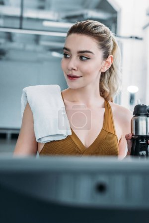 Photo for Smiling sporty girl with towel on shoulder holding sports bottle and looking away in gym - Royalty Free Image