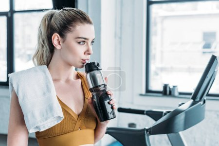 Photo for Beautiful sportswoman with towel on shoulder drinking water from sports bottle in gym - Royalty Free Image