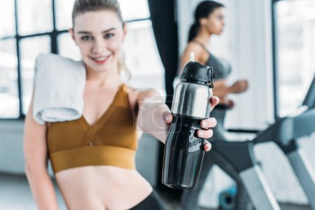 close-up view of beautiful happy sporty girl holding sports bottle with water in gym