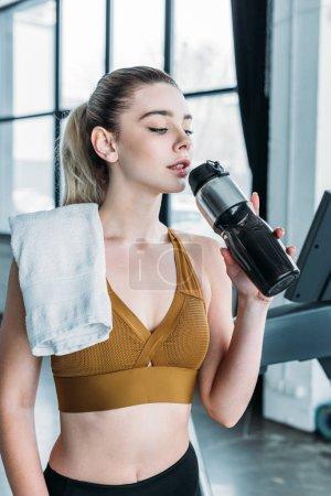 Photo pour Jeune femme sportive avec serviette sur l'épaule boire de l'eau de bouteille de sport dans la salle de gym - image libre de droit