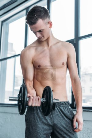 Photo for Muscular shirtless man exercising with dumbbell and looking at biceps in gym - Royalty Free Image