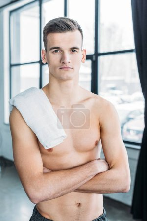 Photo for Handsome shirtless sportsman standing with crossed arms and looking at camera in gym - Royalty Free Image