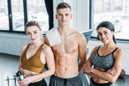 Photo for Shirtless male trainer and beautiful multiethnic sportswomen smiling at camera in gym - Royalty Free Image