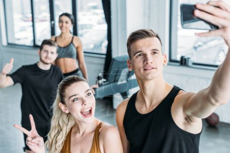 multiethnic group of sportive young friends taking selfie with smartphone in gym