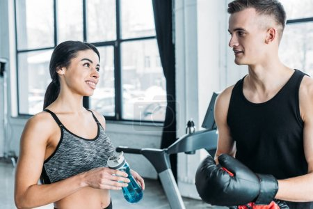 young man with boxing gloves and african american woman with sports bottle smiling each other in gym