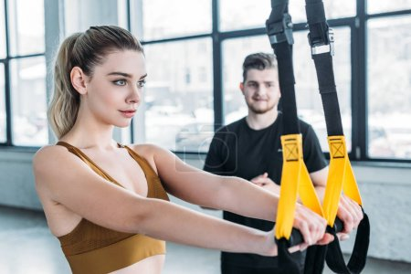 Photo for Young man looking at beautiful sporty girl training with suspension straps in gym - Royalty Free Image