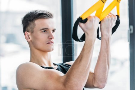 Photo for Handsome muscular young man exercising with suspension straps in gym - Royalty Free Image
