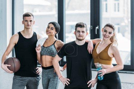 Photo pour Groupe multiethnique de jeunes amis sportifs debout ensemble et souriant à la caméra dans la salle de gym - image libre de droit