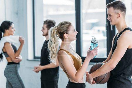 Photo pour Jeune femme tenant une bouteille d'eau et regardant bel homme avec basket-ball dans la salle de gym, couple multiethnique debout derrière - image libre de droit
