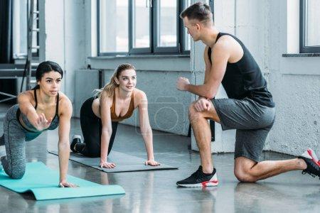 Photo pour Beau jeune sportif regardant les filles sportives multiraciales exercer sur des tapis de yoga dans la salle de gym - image libre de droit