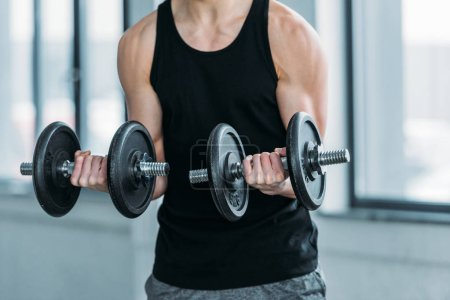 Photo for Cropped shot of muscular young man exercising with dumbbells in gym - Royalty Free Image
