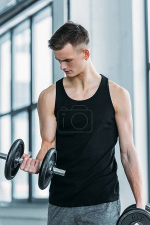 Photo for Handsome young sportsman exercising with dumbbells in gym - Royalty Free Image
