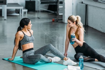 Photo for Smiling sporty multiethnic girls resting on yoga mats and drinking water in gym - Royalty Free Image