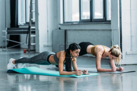 Photo for Sporty multiethnic girls doing plank exercise on yoga mats in gym - Royalty Free Image