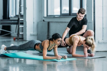 male trainer helping multiethnic girls doing plank exercise on yoga mats in gym