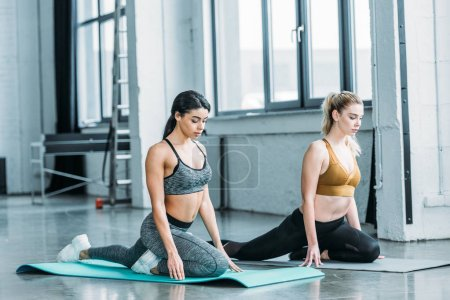 Photo for Beautiful multiracial young women in sportswear training on yoga mats in gym - Royalty Free Image