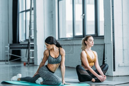 beautiful multiracial sporty girls stretching and training on yoga mats in gym